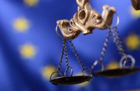 Waage der Justitia vor der europaeischen Flagge von Corgarashu auf adobe-stock.com
