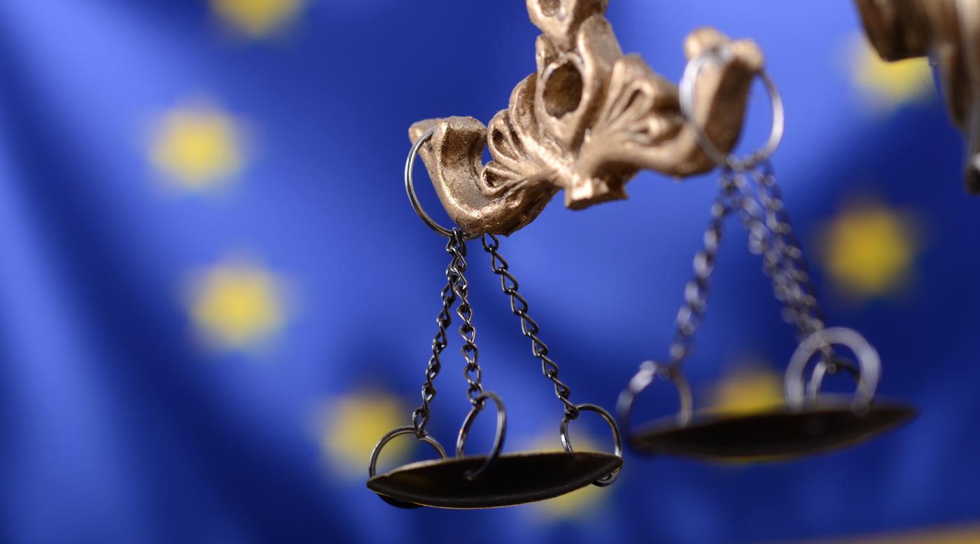 Waage der Justitia vor der europaeischen Flagge
