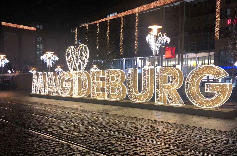 Straße mit Lichtreklame mit Schriftzug Magdeburg.